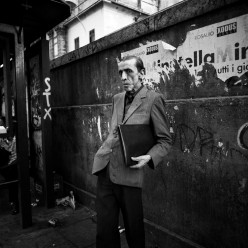 a man waits for the bus at a vandalised bus stop in Palermo