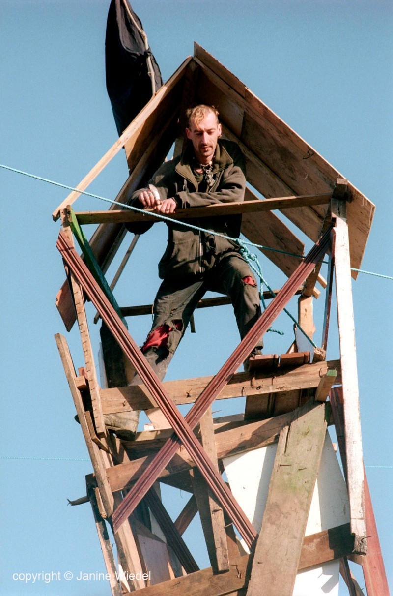 eco warrior climbing up into tower built as lookout defence while protesting at Crystal Palace park over proposed building of multi billion Pound leisure center on parkland.